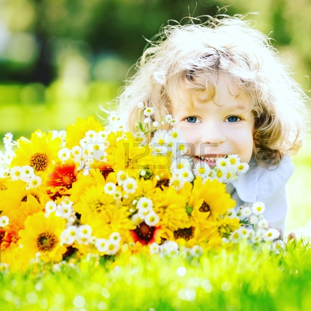 Photograph of young child sitting in flowers